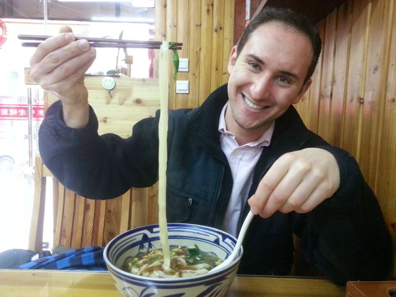 Macaulay student with noodles in restaurant during study abroad trip to China