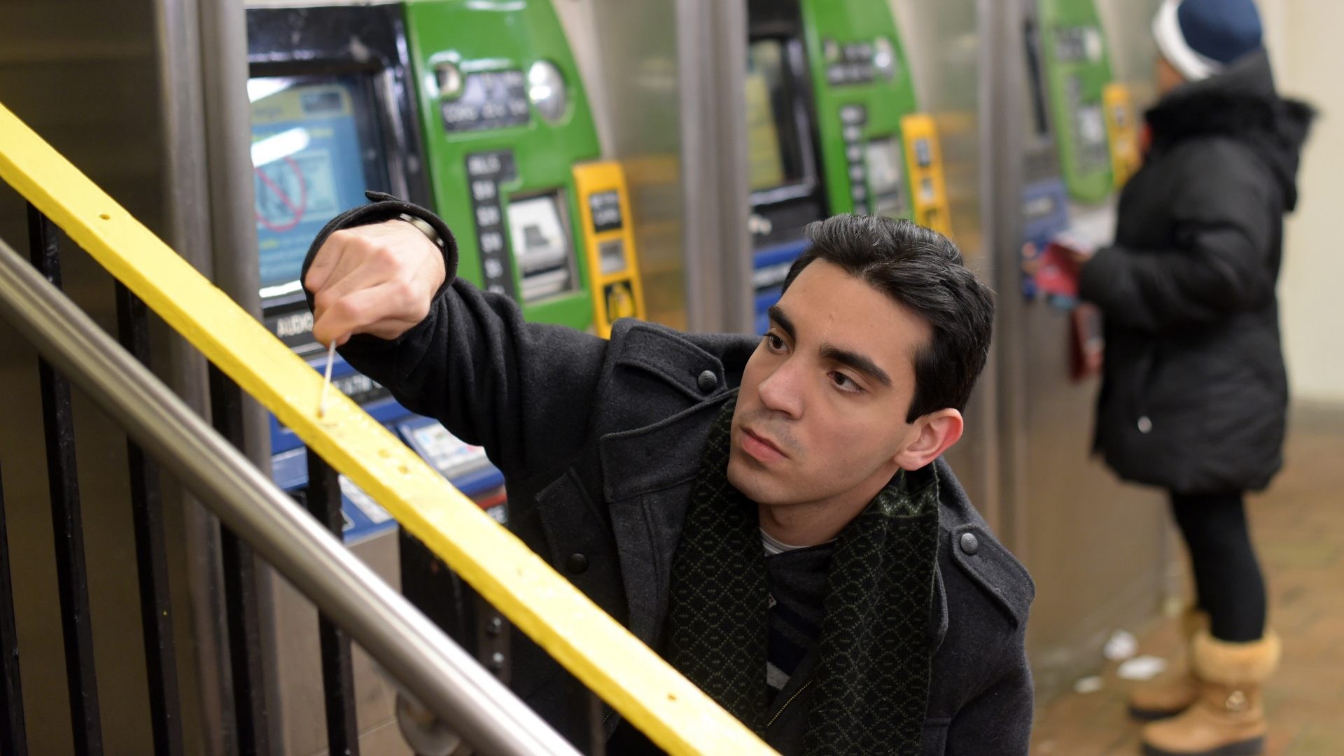 Photo of Macaulay student, Ebrahim Afshinnekoo, taking sample for his research at the train station